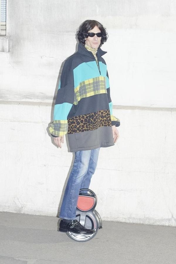 Balenciaga AW18 (1) model wears multi-tiered sweater with panels in light blue, navy, grey, leopard, and yellow tartan; worn with distressed blue jeans.