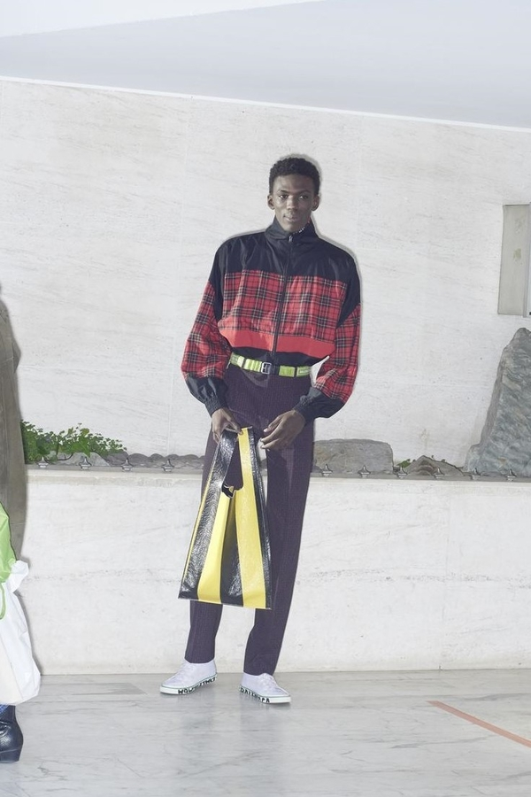 Balenciaga AW18 model wears two-tone red tartan and plain black bomber, black trousers with yellow fabric belt, model carries black and yellow-striped bag.