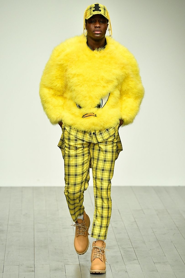 Bobby Abley AW18 (2) model wears cartoon Tweety themed, furry yellow jumper, paired with yellow tartan trousers and beige walking boots.