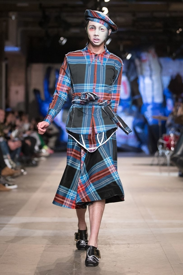 Charles Jeffrey AW18 (1) model wears tartan skirt, shirt, and beret in a red on blue on black colourway