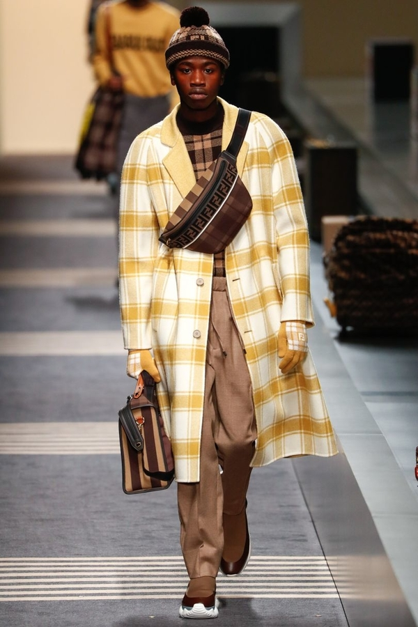 Fendi AW18 (1) model wears yellow and white check overcoat with light brown trousers and brown check jumper, accessorised with matching brown check shoulder bag.