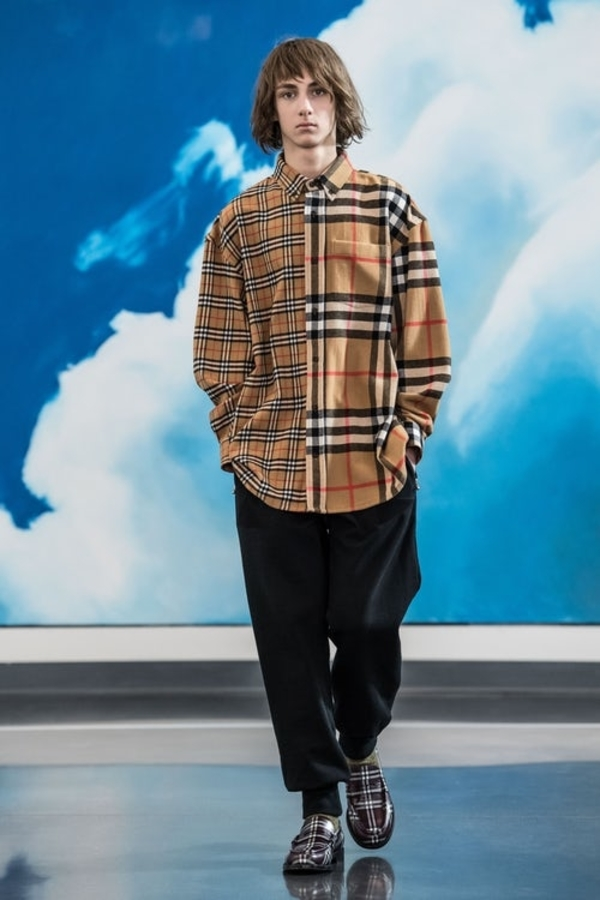 Gosha Rubchinskiy AW18 model wears contrasting shirt in classic burberry check and oversized burberry check, matched with dark joggers and burberry print loafers.