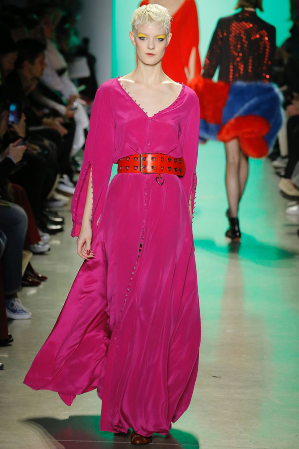 This look from the Adam Selma catwalk is comprised of a flowing, hot pink maxi dress belted at the wait with a red leather belt. Rulo loop button fastenings run up the sleeves and dress length. The model is wearing bold yellow eyeshadow.