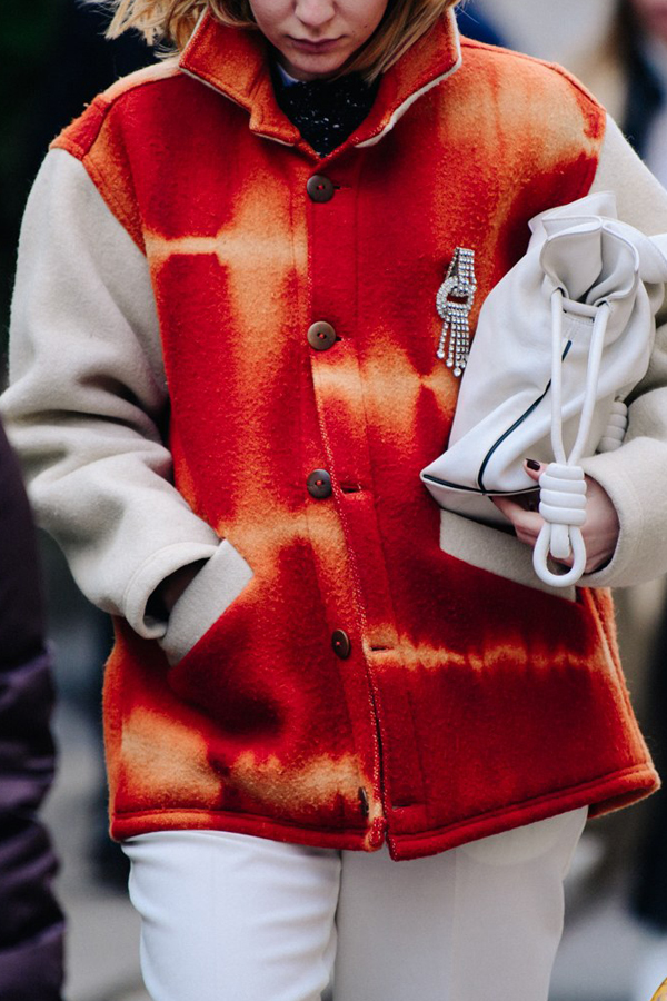 Street Style Picture From Milan Fashion Week Autumn /Winter 2018. Lady wearing white outfit. Felt jacket is orange with bleach fabric manipulation and is decorated with a crystal broach