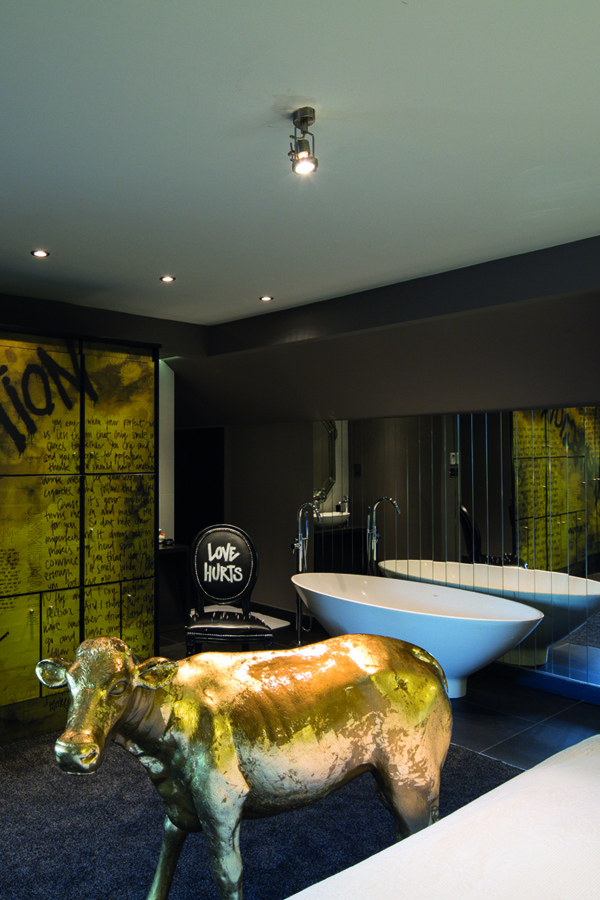 A boutique room at the The Exhibitionist Hotel in London. Featuring graffiti wall art, a cow and a large bath