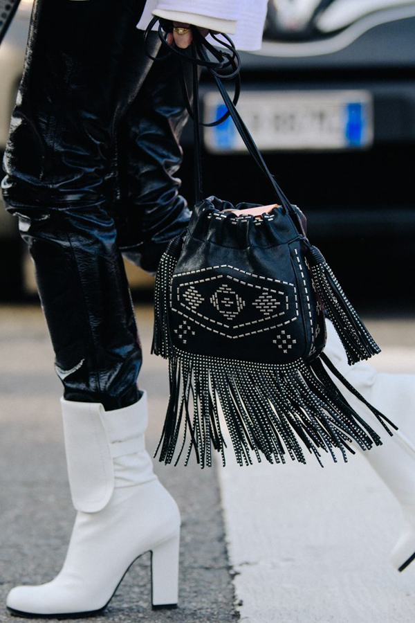 Street Style Picture From Milan Fashion Week Autumn /Winter 2018. Lady wearing black leather trousers and white leather boots. Outfit accessorised with a studded leather bag with fringing.