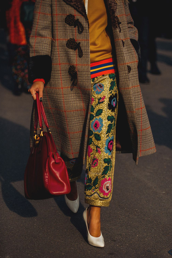 Street Style Picture From Milan Fashion Week Autumn /Winter 2018. Lady wearing vintage check tweed coat with fur cuff. Worn with metallic, embroidered trousers and tracksuit top.