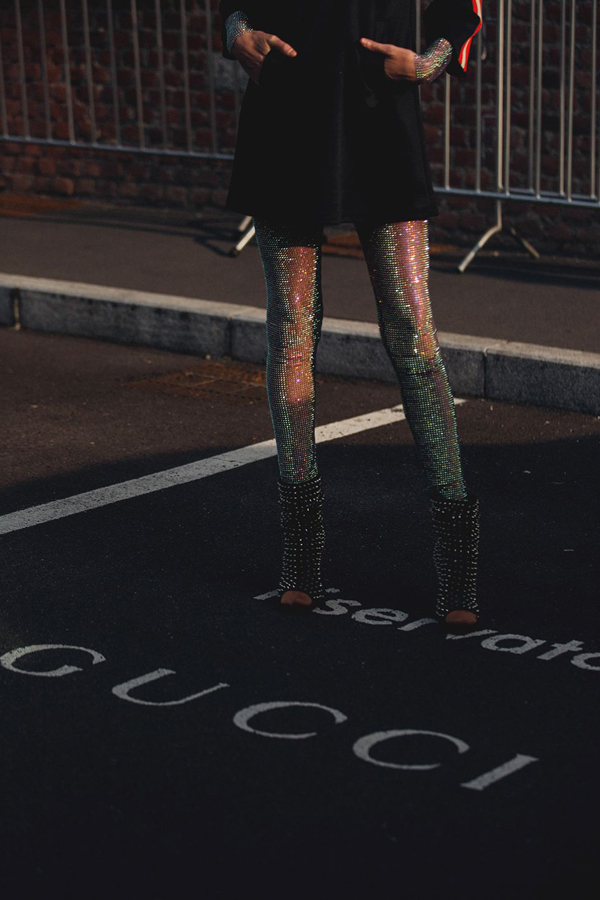 Street Style Picture From Milan Fashion Week Autumn /Winter 2018. Lady wearing metallic leggings under a black playsuit. Outfit accessorised with black leather, studded, heeled, boots. Subject stood in gucci car parking spot