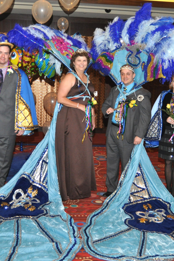 Picture of king and queen of the mardi gras carnival at the parade's ball. Dressed in carnival costume with traditional colours.