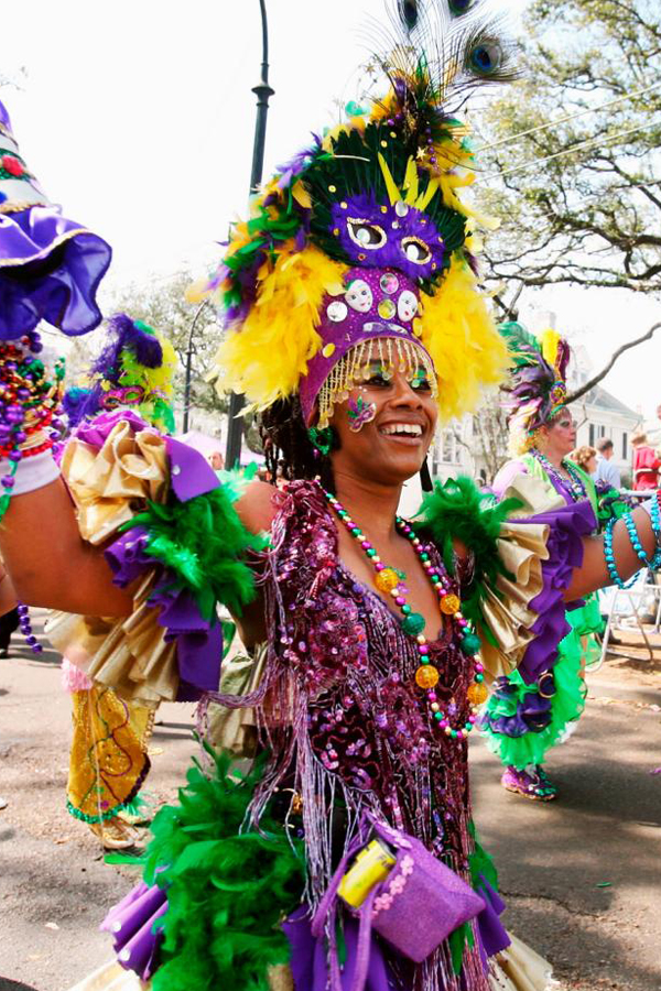 Lady in costume for Mardi Gras Carnival. Wearing purple, green and gold, the colours of the parade and the trophy beads, dancing along to the celebration.
