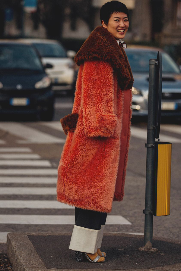 Street Style Picture From Milan Fashion Week Autumn /Winter 2018. Lady wearing monochrome large turn-ups, metallic and glitter sandals with yellow socks, and an orange and brown fur coat.