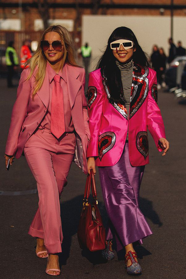 Street Style Picture From Milan Fashion Week Autumn /Winter 2018. Lady wearing vintage check tweed coat with fur cuff. Ladies wearing satin power suits. One lady in all one colour: pink and the other in an embellished jacket.