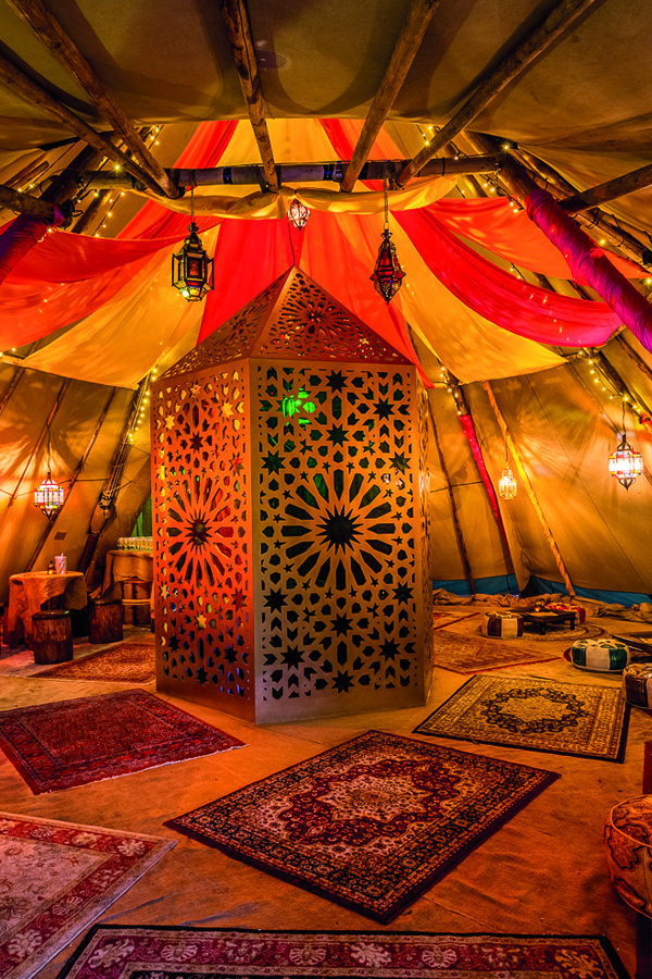 The interior of a tipi on the roof top bar and terrace at the Queen of Hoxton . Decorated with patterned rugs, lanterns and embellished cushions.