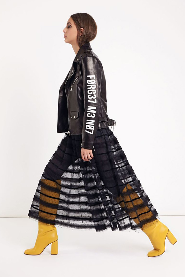 "Red Valentino Look book for A/W 2018. This look features a translucent long skirt with frills and polka dots. A leather jacket with block lettering with the slogan ""forget me not"" and long yellow pic boots accompany the the skirt."