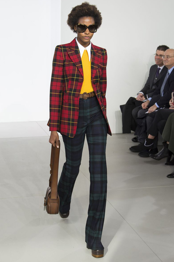 Michael Kors- Autumn/ Winter 2018 Ready-to-wear collection - Vogue - dressed in a fitted, plaid, preppy blazer and flared trousers. Accessorised with platforms, satchel, leather belt and snakeskin sunglasses