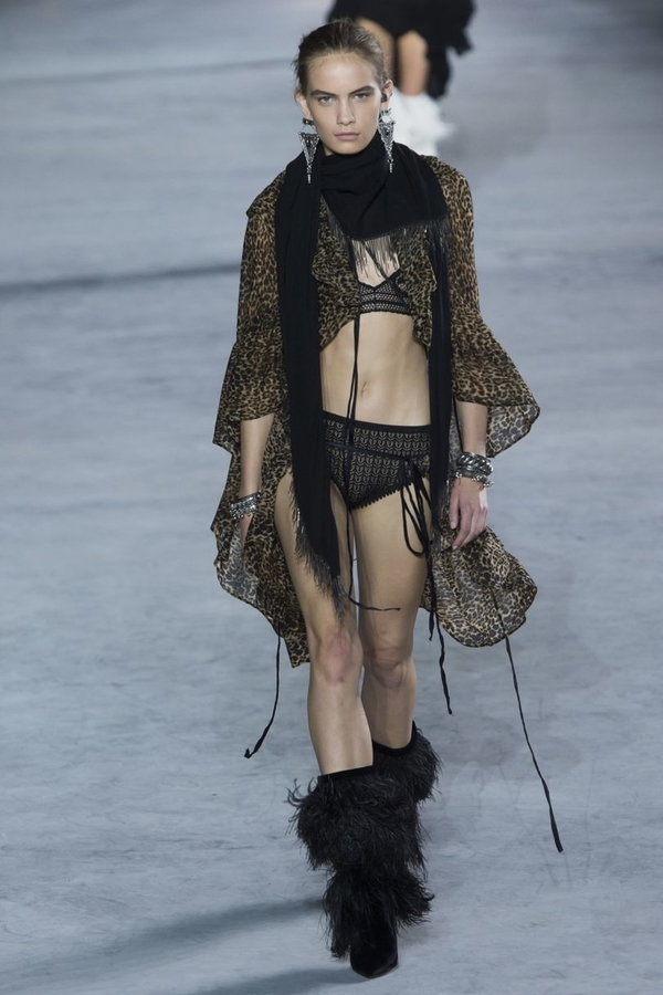 Model wears sheer leopard-print open kaftan over lingerie, with furry black boots and black scarf for Saint Laurent SS18