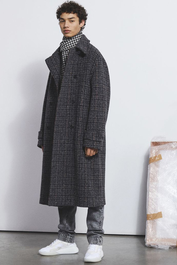 A look from Stella McCartney's Autumn/Winter 2018 Menswear collection combining a tweed, wool coat with on-trend gingham scarf and washed grey jeans for a minimalist style.